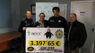 La Policía Local entrega a la junta local de la AECC el cheque con el dinero recaudado por Clawhauser
